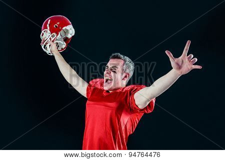 A triumph of an american football player without his helmet with black background