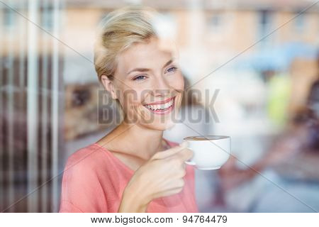 Happy blonde woman drinking a cup of coffee at the coffee shop