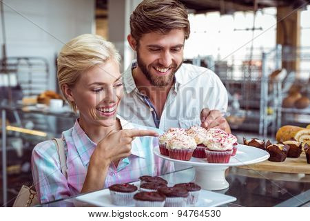 Cute couple on a date pointing chocolate cakes at the bakery