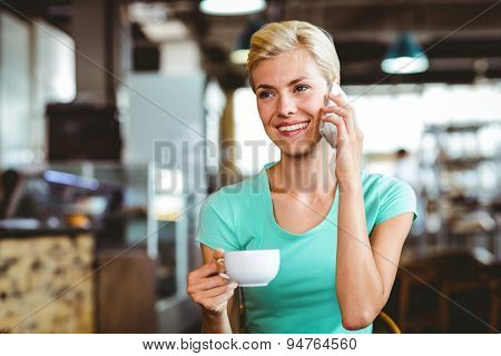 Pretty blonde woman using her smartphone with a cup of coffee at the cafe