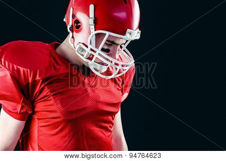 A mercian football player taking his helmet on her head with black background