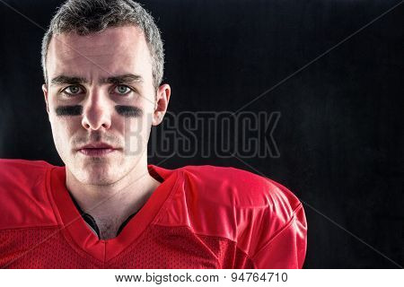 Portrait of a serious american football player looking at camera with black background