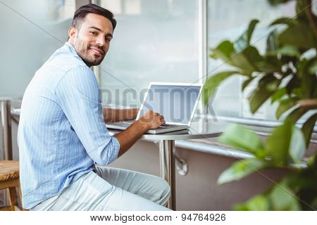Distant view of a smiling businessman using his laptop outside a cafe