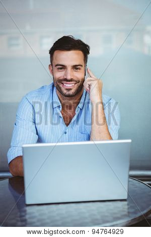 Portrait of a smiling businessman on the phone working on laptop