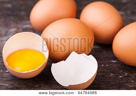 Broken eggs on a wooden background