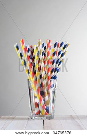 A bunch of multi-colored drinking straws .The straws are fanned out in a drinking glass on a wood table against a light to dark gray background.