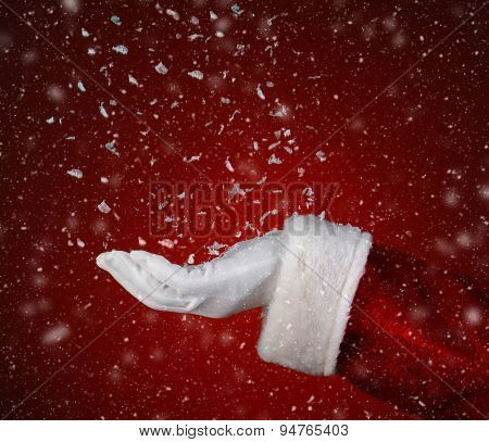 Closeup of Santa Claus catching snowflakes in his hand over a red background. Only hand and sleeve of Santa are visible.