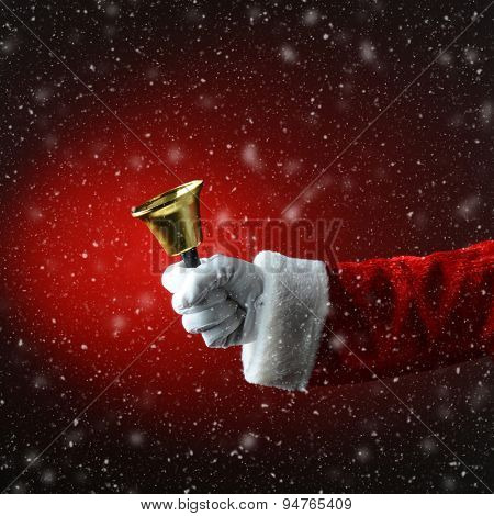 Santa Claus ringing a bell over a snowy light to dark red background.  Only hand and sleeve of Santa are visible.