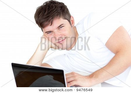 Attractive Young Man Using His Computer Lying On The Floor