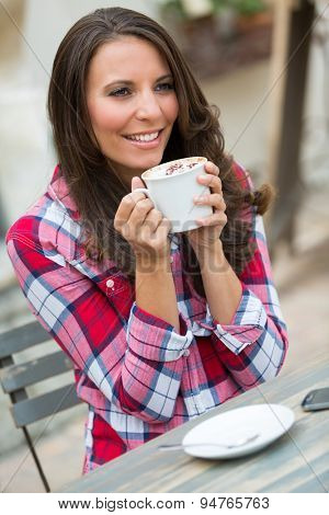 Smiling woman drinking coffee outside