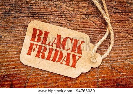 Black Friday sign a paper price tag against rustic red painted barn wood
