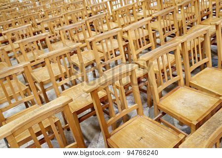 Huge group of wooden chairs arranged in rows.