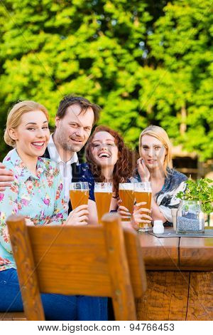 Friends toasting with beer in garden restaurant