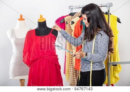 Young Asian Designer Hold Fabric Enrobing It To The Mannequin, Smiling