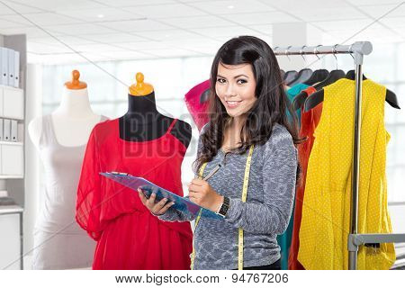 Young Asian Designer With A Clipboard Standing And Smiling