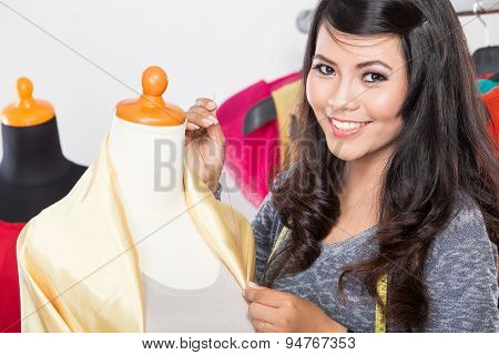 Young Asian Designer Sewing A Fabric On A Mannequin, Smiling To The Camera
