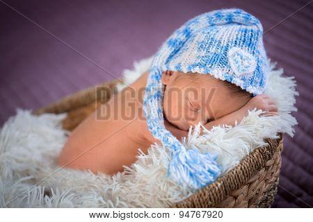 Newborn baby boy sleeping inside the wicker basket