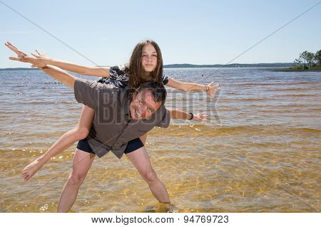 Portrait Of Father Giving Piggyback Ride To Daughter On Beach