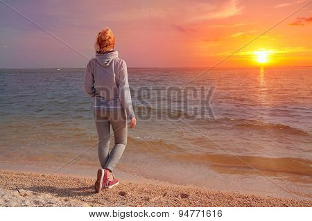 Girl Stands With His Back To The Sea At Sunset. Travel To Europe, Netherlands