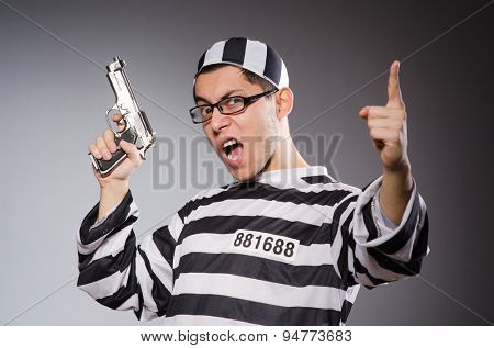 Funny prisoner with firearm isolated on gray