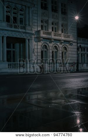 Veritcal close up low angle view of impressive classical concrete building's numerous windows on a wet night illuminated by street lamp London