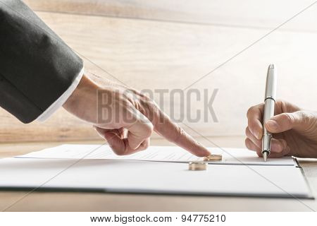 Male Hand Pushing A Wedding Ring Over To A Female Hand About To Sign Divorce Papers