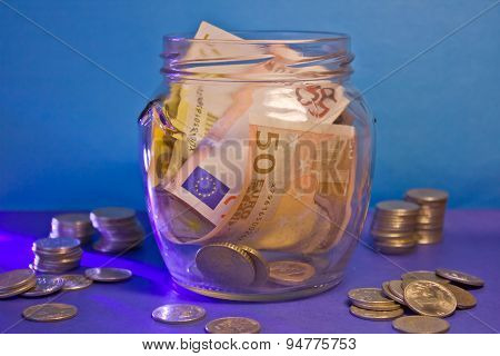 Banknotes and coins in a glass jar