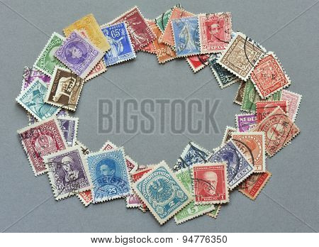 NACHOD, CZECH REPUBLIC - JUNE 6, 2015: Philately - heap of European vintage postage stamps as oval frame on grey cardboard