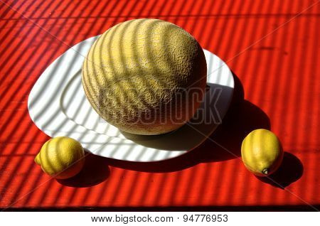 Cubist background with whole sugar melon on plate with two lemons.
