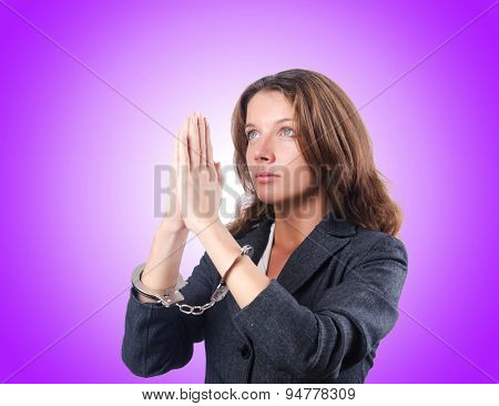 Female businesswoman with handcuffs against gradient