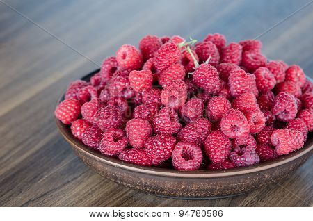 fresh ripe raspberries in clay plate