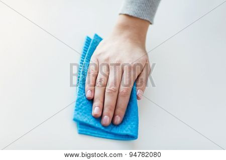 people, housework and housekeeping concept - close up of woman hand cleaning table surface with cloth at home