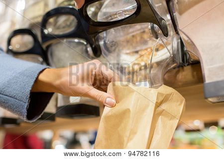 sale, shopping and eco food concept - close up of female hand pouring nuts to paper bag at grocery store