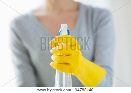 people, housework and housekeeping concept - close up of happy woman with cleanser spraying home