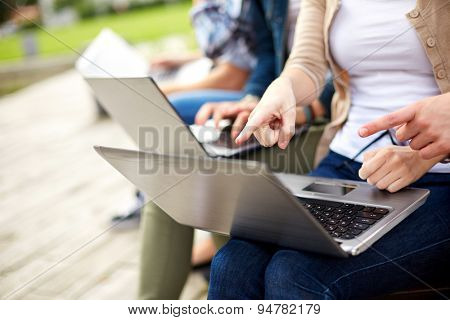 summer, internet, education, campus and people concept - close up of students or teenagers with laptop computers at campus outdoors