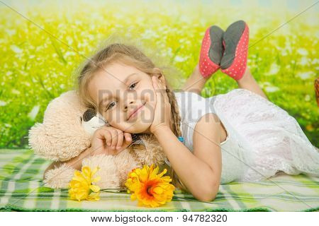 Five-year Girl Hugging A Teddy Bear Lying On Picnic Rug