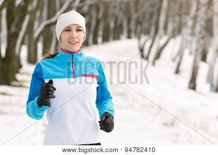 Young Smiling Woman Jogging In Winter Park.