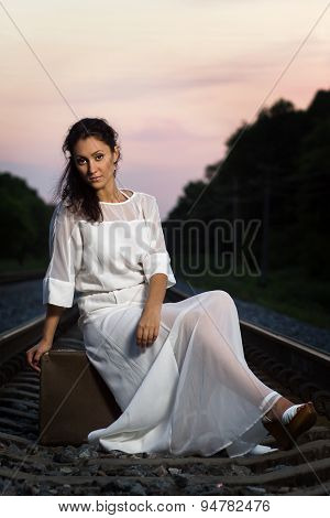 Young Beautiful Woman With Old Suitcase At Railroad