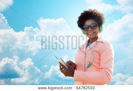 technology, lifestyle and people concept - smiling african american young woman or teenage girl with smartphone and headphones listening to music over blue sky and clouds background