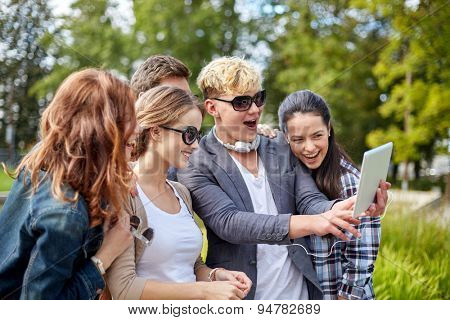 summer, technology, education and teenage concept - group of happy students or teenagers with tablet pc computer taking selfie