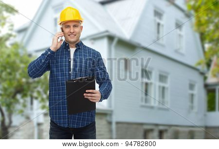 repair, building, construction, real estate and maintenance concept - smiling man or builder in helmet with clipboard calling on smartphone over living house background