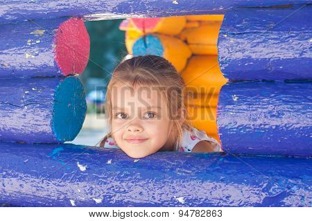 Five-year Girl Looks Out From A Wooden Window