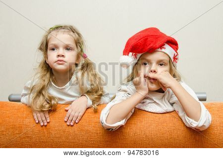 Two Girls Looking To Left Leaning Back On The Couch