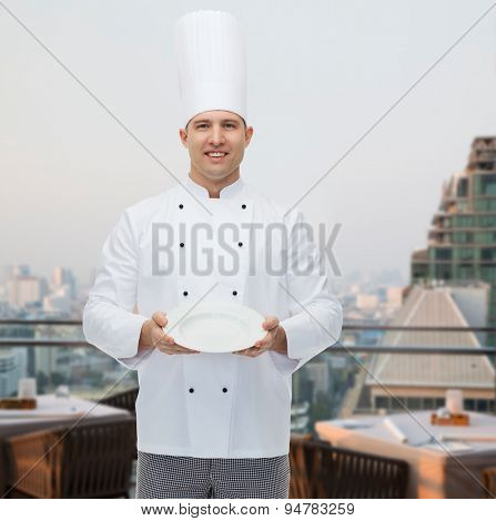 cooking, profession, advertisement and people concept - happy male chef cook showing something on empty plate over city restaurant lounge background