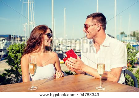 love, dating, people and holidays concept - smiling couple wearing sunglasses with champagne and red gift box looking to each other at cafe