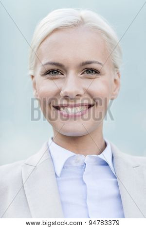 business, people and education concept - young smiling businesswoman over office building