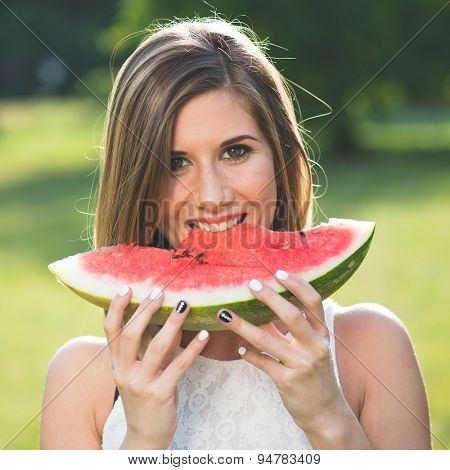 Pretty happy woman eating slice of juicy red watermelon outdoors in park with shallow depth of field