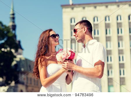 love, wedding, summer, dating and people concept - smiling couple wearing sunglasses with bunch of flowers looking at each other in city