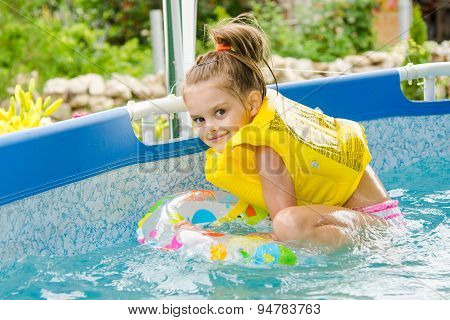 Cheerful Girl Bathing Trying To Get Into The Swimming Circle