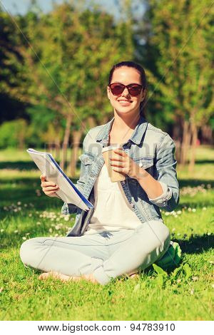 lifestyle, summer vacation, education, drinks and people concept - smiling young girl reading notes from notebook and drinking coffee in park